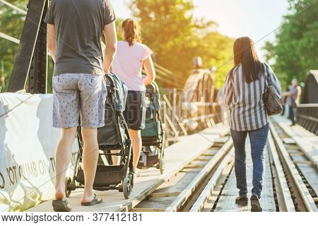 Dad And Mum Take Their Children On A Stroller To Walk And Enjoy The Beauty Of The Bridge Over The Ri