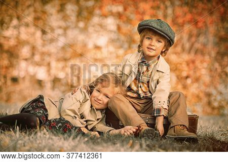 Funny romantic kids boy and girl spending time together in a beautiful autumn park. Children's fashion. Retro style.