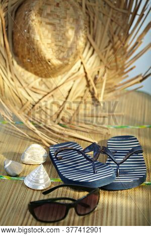 A group of beach objects, shells, sunglasses, straw hat, flip-flop sandal.