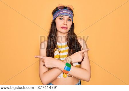 Young beautiful hippie woman with blue eyes wearing accesories and sunnglasses Pointing to both sides with fingers, different direction disagree