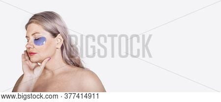 Aged Caucasian Woman With Blonde Hair And Hydrogel Eye Patches Posing With Naked Shoulders On A Whit