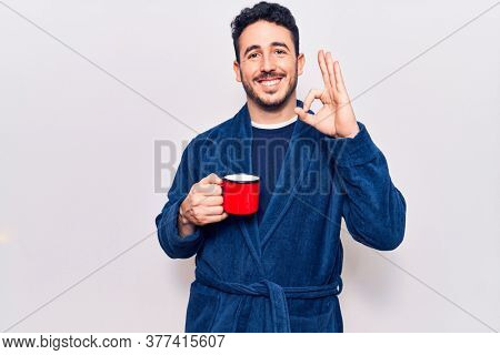 Young hispanic man wearing robe holding coffee doing ok sign with fingers, smiling friendly gesturing excellent symbol