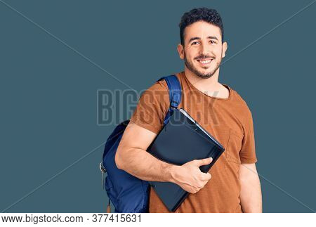 Young hispanic man wearing student backpack holding binder looking positive and happy standing and smiling with a confident smile showing teeth