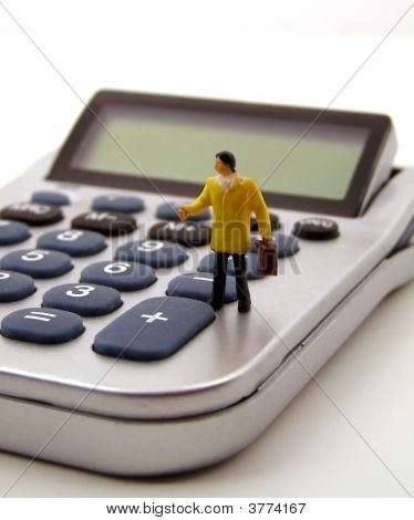 Miniature Accountant Standing On Calculator