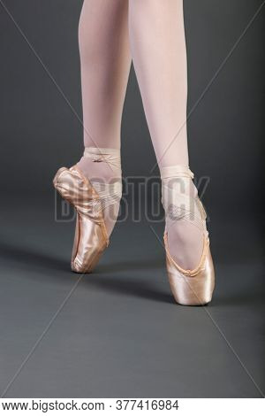 Low section of young female ballet dancer with legs crossed tiptoeing over grey background