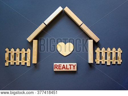 Model Of A Wooden House From Wooden Blocks. Word 'realty'. Wooden Heart And Fence. Copy Space. Busin