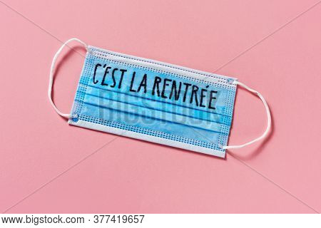 high angle view of a blue surgical mask with the text back to school written in french, on a pink background, depicting the need to prevent the infection at school in the covid-19 pandemic situation