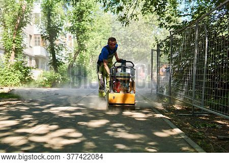 Perm, Russia - July 08, 2020: Worker With Vibratory Plate Compacts Sand Before Laying Paving Slabs