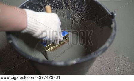 Waterproofing Concrete Floor With Mortar And Brush. An Industrial Worker At A Construction Site Inst