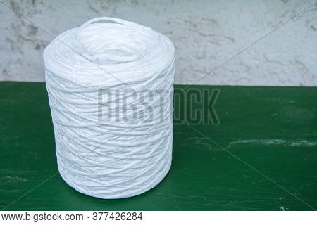 Spool With White Twine On Green Table. Supplies And Tools For Handmade Hobby Leisure.