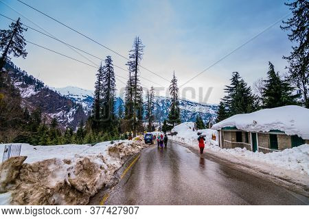 A Landscape Of A Hilly Highway After Rain With Snow Capped Houses By The Side . Snow Capped Mountain