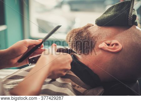 Trendy Barber Carefully Cuts The Beard of Her Constant Client.