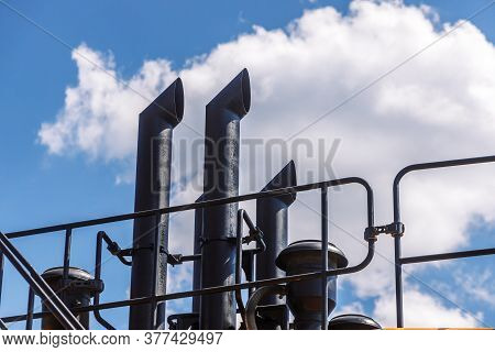 Black Exhaust Pipes On A Large Dump Truck Against The Sky