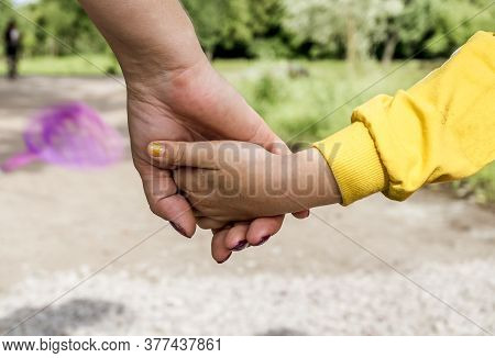 A Woman's Hand Holds The Hand Of A Little Girl Against The Background Of A Forest Landscape