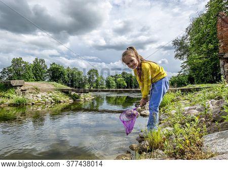 A Girl With A Net On The Bank Of A River On A Sunny Summer Day