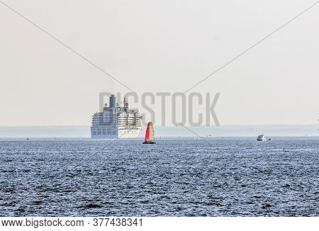 Red Sail Of A Yacht On The Background Of A Huge Cruise Ship In The Open Sea