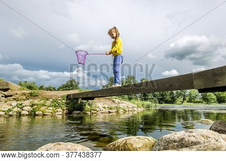 A Girl With A Net Stands On A Bridge Across A River On A Sunny Summer Day