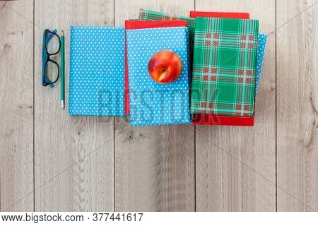 Back To School, Pile Of Books In Colorful Covers And Red Peach On Wooden Table Background. Distance