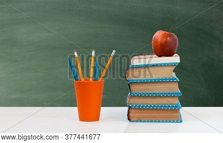 Back To School, Pile Of Books With Empty Green School Board Background. Distance Home Education. Qua