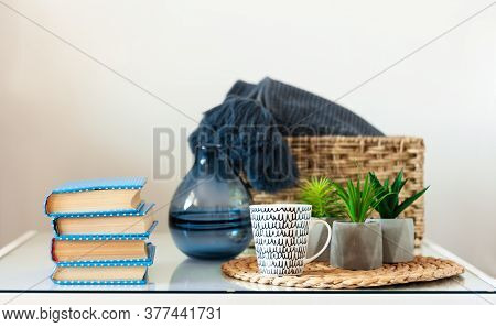Cozy Home Interior Decor: Stack Of Books, Plants In Pots On A Wicker Stand, Pillows And Plaid On A W