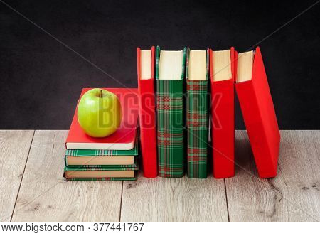 Back To School, Pile Of Books In Colorful Covers And Green Apple On Wooden Table With Empty Black Sc
