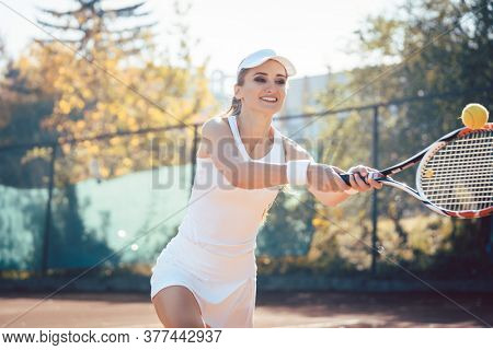 Woman playing tennis on court hitting the ball