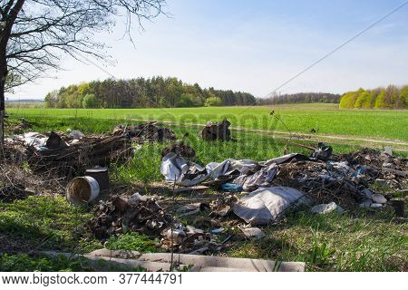 Illegal Garbage Dump In The Middle Of A Green Field And Forest