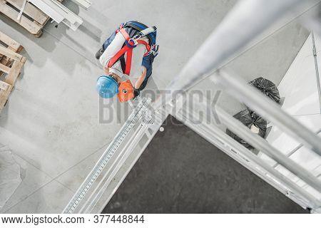 Worker Installing Counter Weight On Aluminium Scaffolding