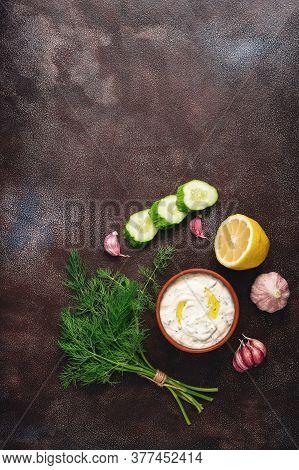 Traditional Greek Tzatziki Sauce With Ingredients On Dark Rustic Background. Greek Yogurt With Cucum