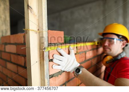 Closeup Of Male Hand Holding Measuring Tape. Brick Stacker Measuring Level Of Wall. Man Building Bri