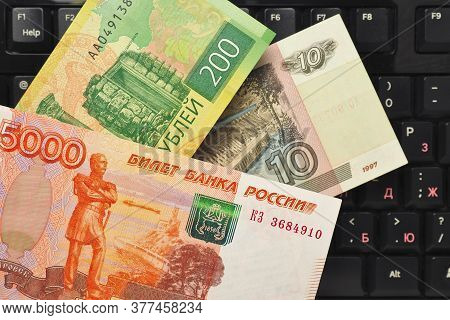 Russian Banknote 5000 Rubles And Others Hang Over The Computer Keyboard. Remote Job, Freelance In Ru