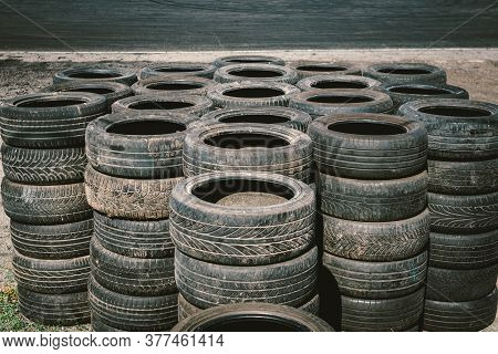 Many Old Used Car Tires Stacked On Top Of Each Other On Automobile Sports Complex. Industrial Landfi