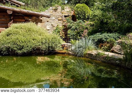 A Courtyard With A Lake, Masonry. Greenery And Water. Cypresses, Cereals. Alpine Slide.