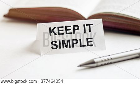 Piece Of Paper With Text Keep It Simple On The Background Of Books, Pens, On A White Background