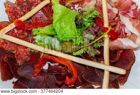 Trio Of Dried Delicacies. Basturma, Prosciutto, Sausage Flat. Plate With Delicacies