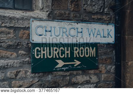 Street Name Sign And A Directional Arrow To Church Room On A Limestone Building On Church Walk In St