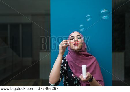 Muslim Girl Blowing Bubbles Outdoors. Muslim Girls Wearing Hiyad. Lifestyle Concept.