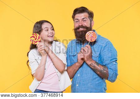 Never Too Delicious. Happy Family Hold Lollipops Yellow Background. Little Child And Father Enjoy De