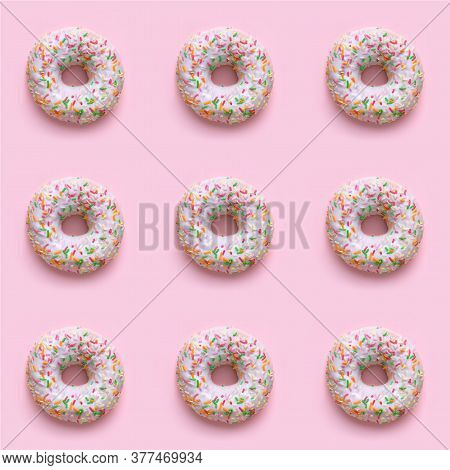 Several Donuts With White Frosting And Colorful Sweet Sugar Sticks.