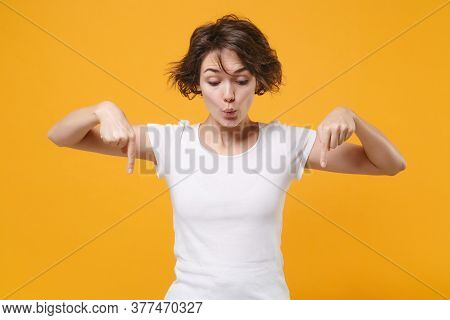 Amazed Young Brunette Woman In White T-shirt Posing Isolated On Yellow Orange Wall Background Studio