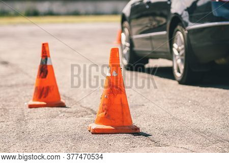 Car And Traffic Cones, Driving School Concept. Old Orange Plastic Cone In Place For Car Driving Trai