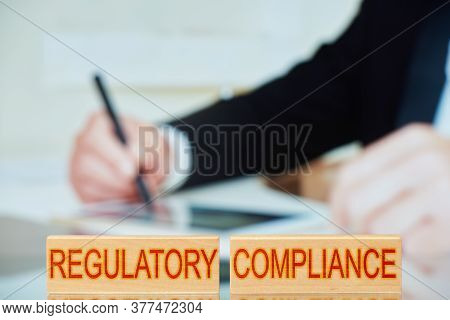 Regulatory Compliance. Wooden Blocks With The Inscription Regulatory Compliance With The Person Sign