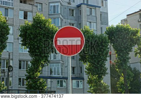 One Round Road Sign No Entry On A Gray Pillar Against The Background Of Green Trees And A Multi-stor