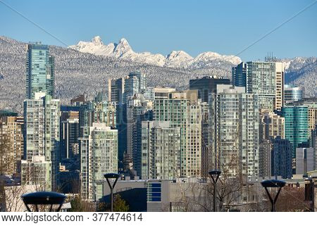 Vancouver Winter Skyline Towers. Office Towers Of Vancouver Against The Peaks Of The Coast Mountains