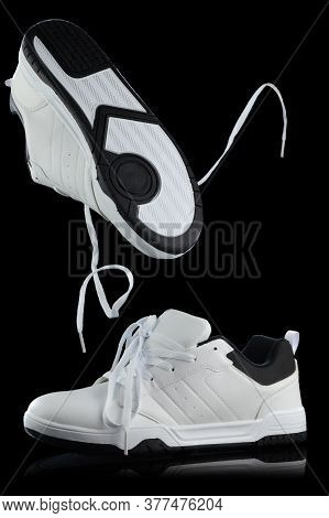 A Stylish Pair Of Mens White Shoes Captured Over A Black Background Making Use Of Studio Secrets To