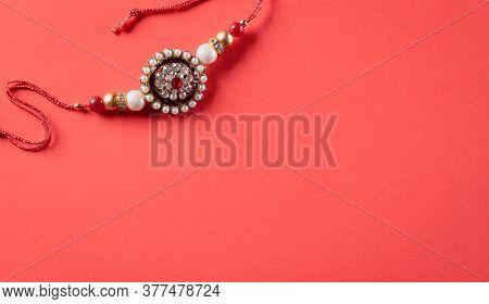 Raksha Bandhan, Indian Festival With Beautiful Rakhi On Red Background.  A Traditional Indian Wrist