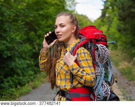 Young Hiker Woman Using A Smartphone In The Forest. Ecotourism Concept.