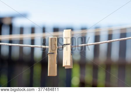 Wooden Clothespins On A Clothesline On The Background Of A Wooden Fence