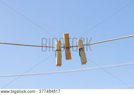 Wooden Clothespins On A Clothesline Against A Blue Sky