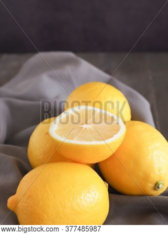 Half And Group Of Fresh Lemon On Grey Fabric Background, With Copy Space. High Vitamin C, Which Help